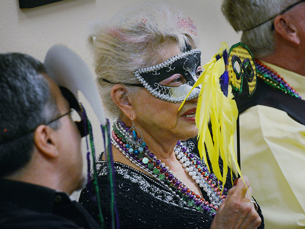 jt030217d/a sec/jim thompson/Maria Causby goes for the mask behind the mask at the Mardi Gras celebration at the Meadowlark Senior Center.  Thursday March 02, 2017. (Jim Thompson/Albuquerque Journal)