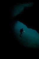 Diver exploring a cavern in the vicinity of Gam Island, Raja Ampat Islands, Indonesia
