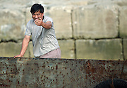 """A North Korean sailor beckons Chinese tourists to come closer fron his a boat in the river town of Sinuiju July 8, 2006. China and North Korea are separated by the Yalu River, upon which Chinese tourists take pleaure cruises across the water to  observe their less economically developed neighbors.  North Korea has threatened to take """"stronger physical actions"""" after Japan imposed punitive measures in response to its barrage of missile tests and pushed for international sanctions. North Korea has vowed to carry out more launches and has said it will use force if the international community tries to stop it. DPRK, north korea, china, dandong, border, liaoning, democratic, people's, rebiblic, of, korea, nuclear, test, rice, japan, arms, race, weapons, stalinist, communist, kin jong il"""