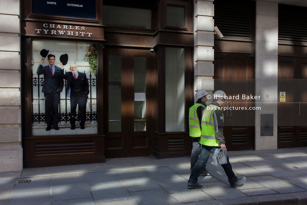 Two manual labourers walk past the Charles Tyrwhitt menswear outfitters at Liverpool Street in the City of London, the capital's heart of its financial district - a good location for suits and businesswear. A pair of Englishmen raise their bowler hats in a gesture from a previous era, when hats said much of your social standing, a summary of your position in the class system. In the 21st century though, the hat is largely an item of clothing to wear only for extreme cold or heat