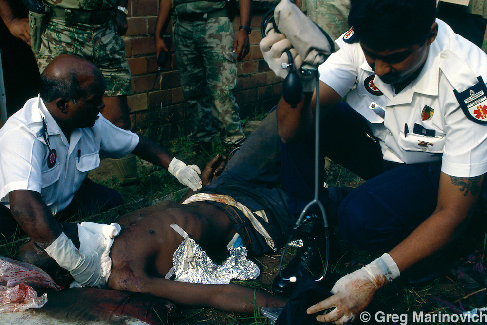 Umlazi township, KwaZulu Natal,South Africa 1995, paramedics treat a wounded person shot from a train.