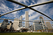 View through the trellis structure at the Frank Gehry-designed Jay Pritzker Pavilion in Millennium Park, Chicago, Il. USA. And downtown cityscape.