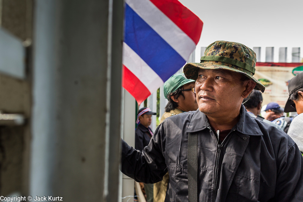 24 DECEMBER 2013 - BANGKOK, THAILAND:  An anti-government protestor looks into the Thai Japan Stadium during a protest in Bangkok. Hundreds of anti-government protestors are camped out around the Thai-Japan Stadium in Bangkok, where political parties are supposed to register for the election on February 2. As of Dec 24, nine of the more than 30 parties were able to register. Protestors hope to prevent the election. The action is a part of the ongoing protests in Bangkok that have caused the dissolution of the elected government.     PHOTO BY JACK KURTZ