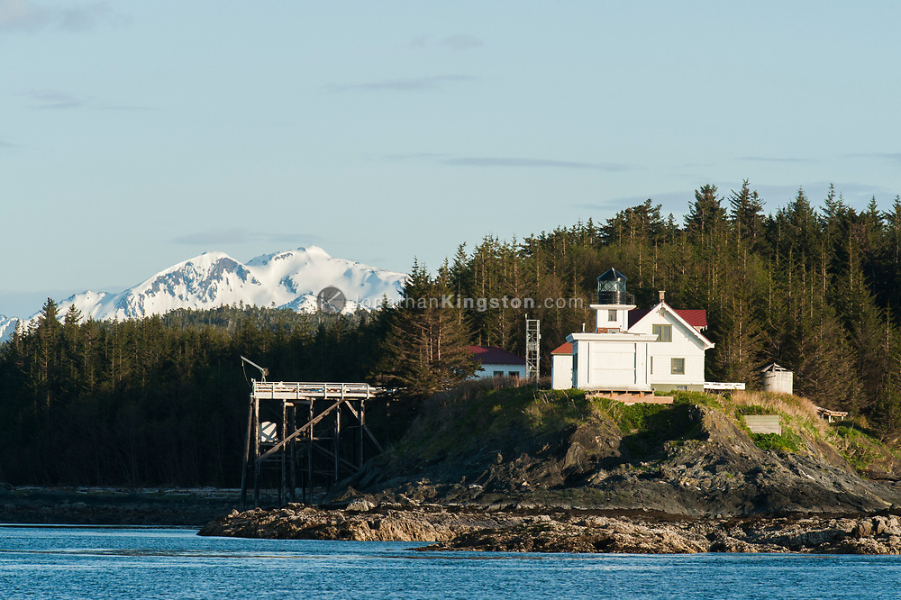 A lighthouse with snow capped mountains in the background.