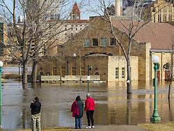 March 29, 2019 - St. Paul, Minnesota, U.S - People look at a flooded building on Harriet Island in St. Paul. The Mississippi River through the Twin Cities has already hit flood stage. Several roads and parks in St Paul are already closed in anticipation of higher flood levels. Weather forecasters and hydrologists have backed off a little on earlier predictions of severe flooding because the snow melt has been slower than expected. (Credit Image: © Jack Kurtz/ZUMA Wire)