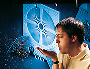Metallic flakes wafting from his hand, Kris Pister of the University of California at Berkeley demonstrates one possible offshoot of robotics research: Smart Dust. Miniature machines, each the size of a dust mite, may eventually saturate the environment, invisibly performing countless tasks. From the book Robo sapiens: Evolution of a New Species, page 26-27.