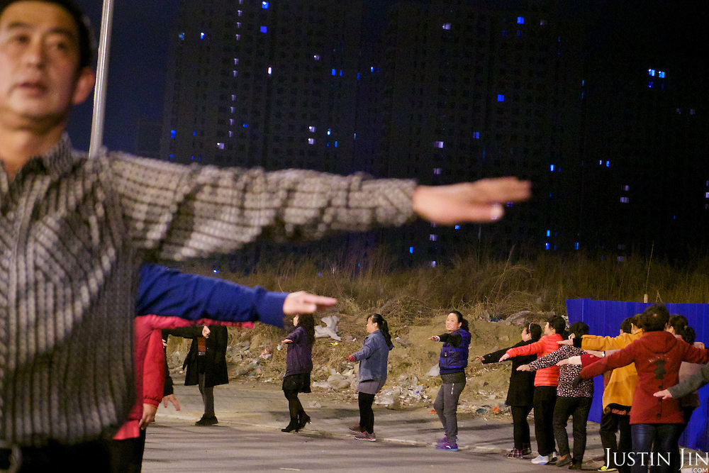 Landless farmers practise group exercise on an urban area built over their farmland in Hubei province on the outskirt of Beijing.<br /> <br /> China is pushing ahead with a dramatic, history-making plan to move 100 million rural residents into towns and cities over six years &mdash; but without a clear idea of how to pay for the gargantuan undertaking or whether the farmers involved want to move.<br /> <br /> Moving farmers to urban areas is touted as a way of changing China&rsquo;s economic structure, with growth based on domestic demand for products instead of exporting them. In theory, new urbanites mean vast new opportunities for construction firms, public transportation, utilities and appliance makers, and a break from the cycle of farmers consuming only what they produce.<br /> <br /> Urbanization has already proven to be one of the most wrenching changes in China&rsquo;s 35 years of economic reforms. Land disputes rising from urbanization account for tens of thousands of protests each year.