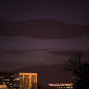 Comet PanSTARRS appears just above the horizon and skyline of Denver, Colorado, 3/13/13.