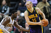 Feb. 21, 2012; Indianapolis, IN, USA; New Orleans Hornets center Chris Kaman (35) looks to pass off the ball as Indiana Pacers center Roy Hibbert (55) guards at Bankers Life Fieldhouse. Indiana defeated New Orleans 117-108. Mandatory credit: Michael Hickey-US PRESSWIRE