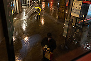 Seen from a London bus on a rainy night in the West End, a man carries drinks on a tray as another hauls some outdoor seating outside a McDonalds o Charig Cross Road, on 27th August 2020, in London, England.