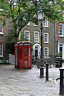 Two scruffy traditional red phone boxes richmond upon thames greater london on cobbled walkway near richmond green