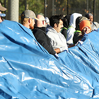 Inmate workers and Tupelo City employees work together to move a portion of the Joyner bubble into place at that will cover a section of the tennis courts at Rob Leake Park on Tuesday morning.
