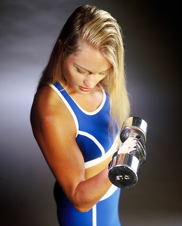 Young woman doing concentration curls with dumbell