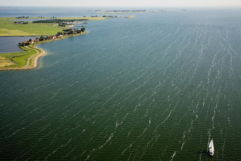 Nederland, Noord-Holland, Uitdam, 14-07-2008; zeilboot op IJsselmeer ter hoogte van Uitdam, Marken aan de hozizon; links de Waterlandse Zeedijk tussen IJsselmeer en Uitdammer Die; Uitdammerdijk; watersport, boot, zeilen, wind, windveren. .luchtfoto (toeslag); aerial photo (additional fee required); .foto Siebe Swart / photo Siebe Swart
