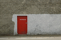 A partially whitewashed wall contrasts with a bright red door along a side street in rural Ireland.