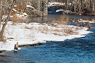 Cuddebackville, New York - A man fishes in the Neversink River on the opening day of trout season in New York State. Most of the riverbank is still covered in snow and ice.