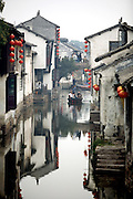 """A boat makes its way down an alley in the """"water village"""" of Zhouzhuang in China's Jiangsu Province."""
