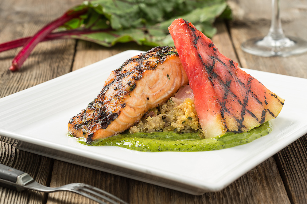 Grilled salmon and watermelon over quinoa with green herb sauce on a rustic background.
