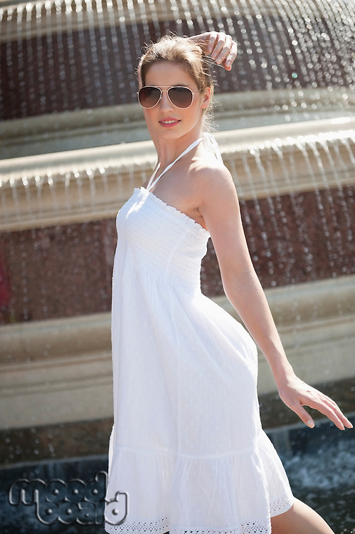 Side view of happy young woman in white halter neck dress standing by water fountain