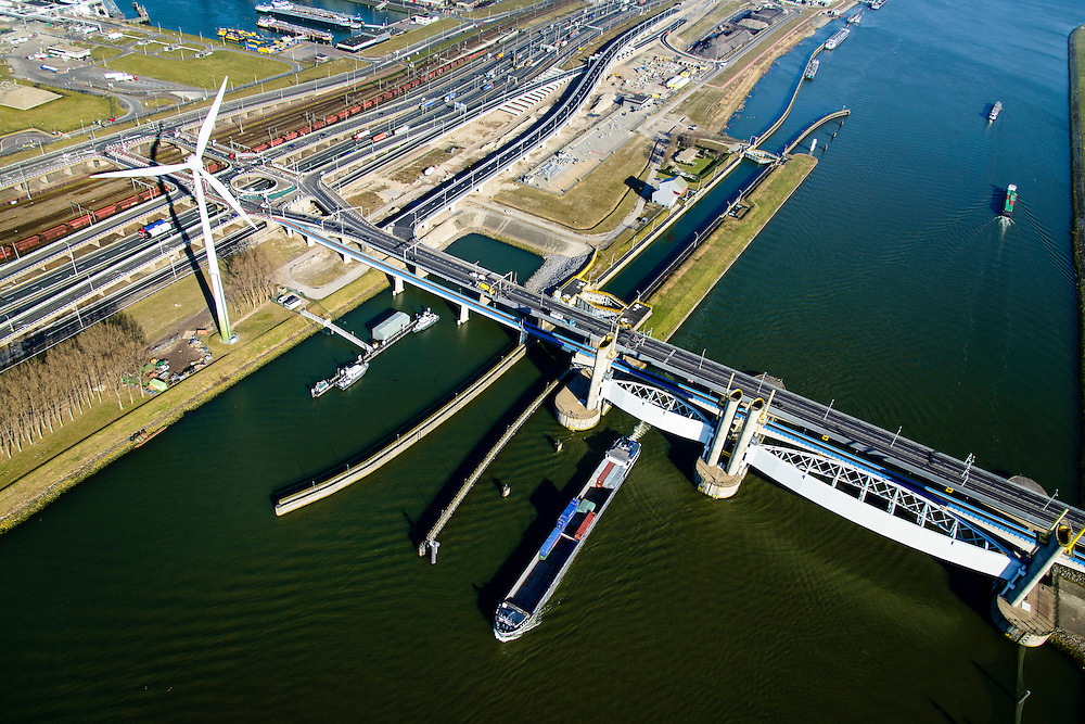 Nederland, Zuid-Holland, Rotterdam, 18-02-2015; Botlek, Hartelkanaal met Hartelkering (stormvloedkering). De kering, onderdeel van de Deltawerken, vormt samen met de Maeslantkering de Europoortkering en beschermt Rotterdam en achterland bij extreme waterstanden. In de achtergrond  Hartelkruis en A15 met Betuweroute.<br /> Storm surge barrier Hartelkering in the Hartel canal. Together with the greater nearby Maeslant barrier (in the New Waterway), the barrier proyect nearby Rotterdam and its hinterland.<br /> luchtfoto (toeslag op standard tarieven);<br /> aerial photo (additional fee required);<br /> copyright foto/photo Siebe Swart