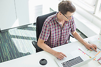 High angle view of creative businessman working at desk in office