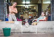 THAILAND, Bangkok: 07 November 2015 A local trading family and their dog at Paak Klong Market, one of Bangkok's leading flower and vegetable markets. Rick Findler / Story Picture Agency