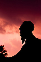 Statue of Ho Chi Minh silhouetted against a later afternoon stormy sky.