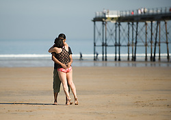 © Licensed to London News Pictures. 28/03/2012..Saltburn, England..As temperatures rise this week the beach at Saltburn in Cleveland attracts the visitors as they enjoy the warm weather. A couple embrace on the beach as they enjoy the warm temperatures...Photo credit : Ian Forsyth/LNP