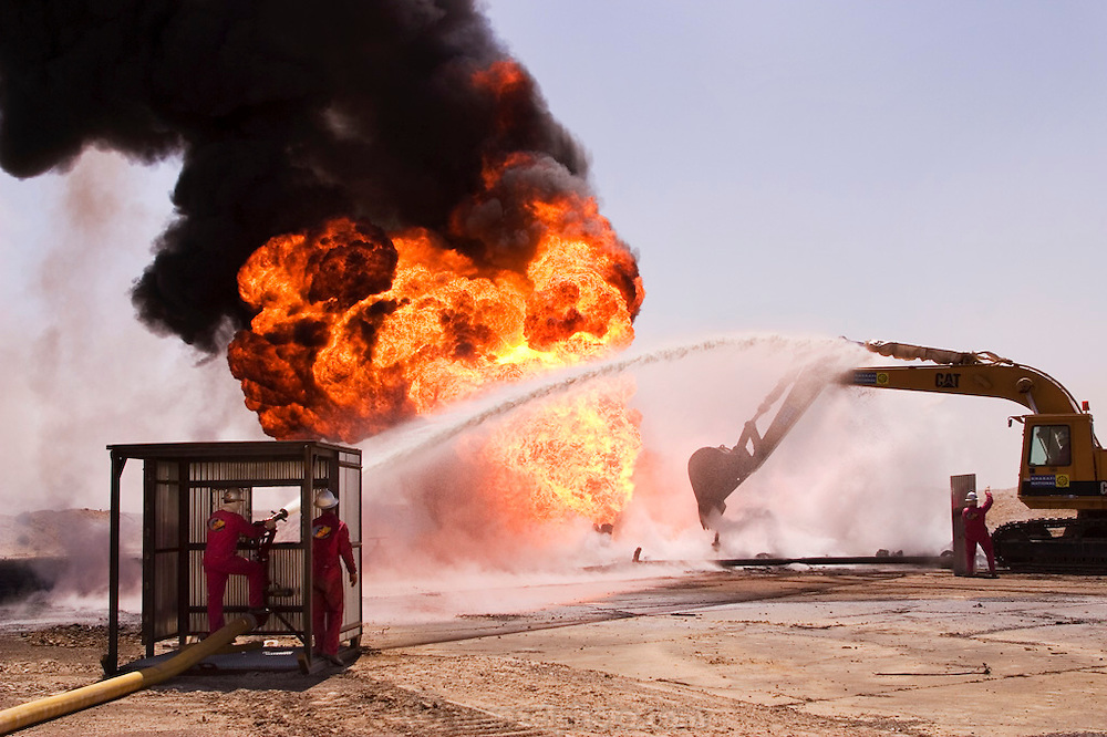 Boots and Coots attack their first oil well fire in the Rumaila field after a delay of a week due to security, sandstorms, and bureaucracy problems. They are using a heat-hardened backhoe to scrape away debris from around the burning wellhead while team members cool the equipment with a constant water spray. The Rumaila field is one of Iraq's biggest oil fields with five billion barrels in reserve. Many of the wells are 10,000 feet deep and produce huge volumes of oil and gas under tremendous pressure, which makes capping them very difficult and dangerous. Rumaila is also spelled Rumeilah.