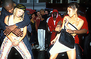 Girls dancing close with men in the street, Notting Hill Carnival 2000's