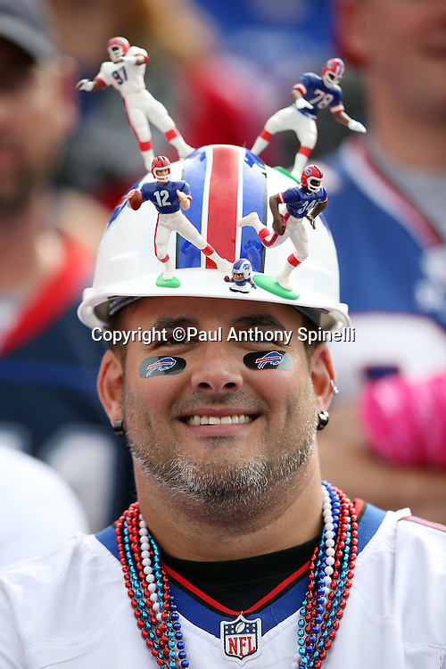 A Buffalo Bills fan wears stick on eye black and a helmet with plastic figurines of former Bills players during the Buffalo Bills 2015 NFL week 4 regular season football game against the New York Giants on Sunday, Oct. 4, 2015 in Orchard Park, N.Y. The Giants won the game 24-10. (©Paul Anthony Spinelli)
