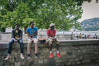 COMO, ITALY - 21 JUNE 2017: A group of migrants from Guinea sit on a wall by Lake Como in Como, Italy, on June 21st 2017.<br /> <br /> Residents of Como are worried that funds redirected to migrants deprived the town's handicapped of services and complained that any protest prompted accusations of racism.<br /> <br /> Throughout Italy, run-off mayoral elections on Sunday will be considered bellwethers for upcoming national elections and immigration has again emerged as a burning issue.<br /> <br /> Italy has registered more than 70,000 migrants this year, 27 percent more than it did by this time in 2016, when a record 181,000 migrants arrived. Waves of migrants continue to make the perilous, and often fatal, crossing to southern Italy from Africa, South Asia and the Middle East, seeing Italy as the gateway to Europe.<br /> <br /> While migrants spoke of their appreciation of Italy's humanitarian efforts to save them from the Mediterranean Sea, they also expressed exhaustion with the country's intricate web of permits and papers and European rules that required them to stay in the country that first documented them.