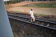A policeman is patrolling a railroad track at a train station in Ubon Ratchathani Province, Thailand.