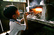 Young boy helps his mother build a fire in their kitchen in preparation for dinner in Vietnam