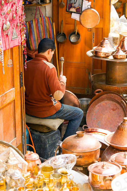 Fez, Morocco - 1st FEBRUARY 2018 - Copper-smith and brass worker artisans work at a market stall selling metal pots and pans in Place Seffarine, old Fez Medina, Middle Atlas, Morocco.