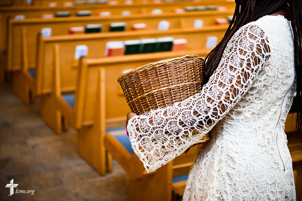 An offering basket is carried to the altar during worship at Lamb of God Lutheran Church, housed in Ascension Lutheran Church, Landover Hills, Md., on Sunday, Aug. 6, 2017. LCMS Communications/Erik M. Lunsford