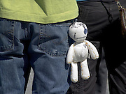 close up of a boy with a little doll hanging from his back pocket