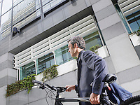 Business man carrying bicycle outdoors low angle view side view