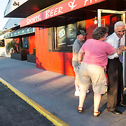 Vickie Linehan (middle) gives Charlie Crist a hug while her brother Rod Glenn (left) watches the two laughing outside Sidelines Sports Bar and Grill in Fort Myers. (Willie J. Allen Jr.)