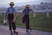 Amish children on roller skates going to their one-room school with lunch pail, Lancaster Co., PA
