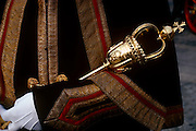 "A Beadle mace-bearer from the City of London holds a ceremonial mace in the crook of his left arm during the annual Lord""s Mayor's Show. Wearing white gloves and a decorative overcoat worn on special occasions, we see only the arm and the golden mace as a close-up detail. The Beadle's role is now only symbolic, accompanying the City Adlermen as the lead the processions through the capital's ancient financial heart. A Beadle or bedel was a lay official of a church or synagogue who would usher, keep order, make reports, and assist in religious functions; or a minor official who carries out various civil, educational, or ceremonial duties. The term has Franco-English pre-renaissance origins, derived from the Vulgar Latin ""bidellus"" or ""bedellus"", rooted in words for ""herald"". It moved into Old English as a title given to an Anglo-Saxon officer who summoned householders to council."
