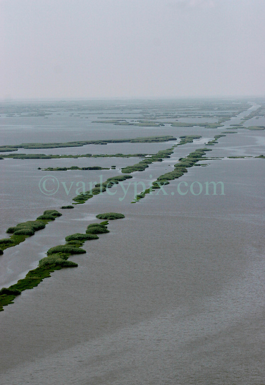 12 june 2010. Wetlands of Plaquemines Parish, South Louisiana. <br /> Vanishing wetlands. Where once there was land, there is only the mere outline of old canals and channels, many dug by oil companies to pump their product ashore with little regard to the effects the chopping up of the wetlands would have. Chronic erosion of the land, a football pitch every 50 minutes, greatly reduced protection from hurricanes and impending BP oil slicks is the direct result of mismanagement and utter disregard for the environment. The army corps of engineers and the oil companies, together with inept government have a great deal to answer for. <br /> View from a blackhawk helicopter flown by airmen of the Nebraska Air National Guard over southern Louisiana as they assist in the dumping of sand bags onto barrier islands in a vain attempt to prevent BP oil from getting into the inner  wetlands. As valiant as their efforts are, the dumping of sand bags may well prove to be a complete waste of manpower, resources and money. Meanwhile, the mighty Mississippi river runs straight out to sea nearby, her valuable land building sediment carried far out into deep ocean as the region struggles to find a way to reverse the disastrous effects of man's interference with her flow. <br /> Photo credit; Charlie Varley/varleypix.com
