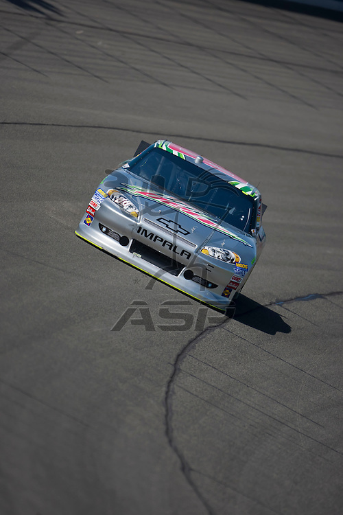 FONTANA, CA - MAR 23, 2012:  Dale Earnhardt, Jr. (88) brings his race car through turn 4 during a practice session for the Auto Club 400 race at the Auto Club Speedway in Fontana, CA.