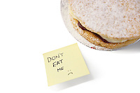Piece of Victoria sponge cake with 'don't eat me' sign on sticky notepaper