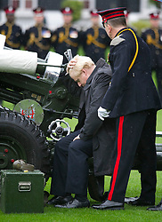 © London News Pictures. 05/11/2013 . London, UK.  Mayor of London BORIS JOHNSON, examines the gun before firing a gun salute to launch London Poppy Day at The Honourable Artillery Company in London. The Mayor fired a salute from a 105mm light gun to launch this year's campaign, which aims to raise more than £1million in just one day. Photo credit : Ben Cawthra/LNP