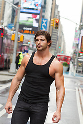 man in a tank top walking in New York City