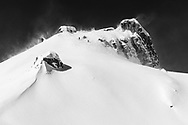 Two ski tourers are climbing up to mount Rau Stöckli in heavy wind gusts, Muotathal, Schwyz, Switzerland
