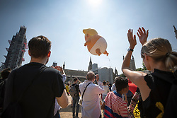 © Licensed to London News Pictures. 13/07/2018. London, UK. People applaud as a giant inflatable balloon depicting President Trump as a baby is lowered after being flown over Parliament Square. President Trump is on the second day of a four day visit to the UK. Photo credit: Peter Macdiarmid/LNP