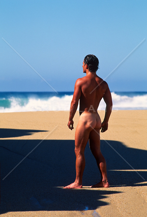 muscular naked man standing on a beautiful beach in Mexico