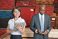 Multiethnic business colleagues using tablet PC and cell phone with stacked wooden planks in background